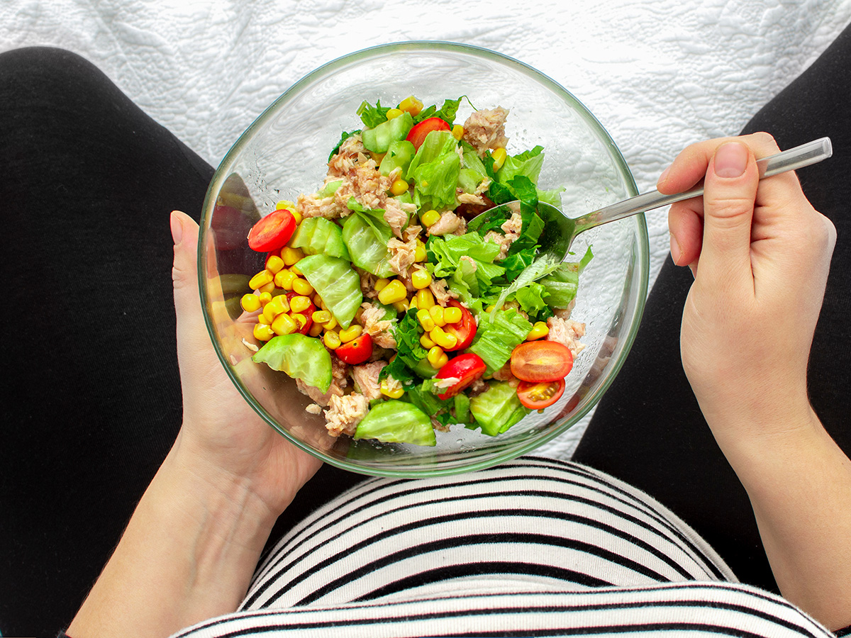 Can you eat fish during pregnancy? Eat Seafood While Pregnant: Picture depicts woman eating tuna salad while pregnant